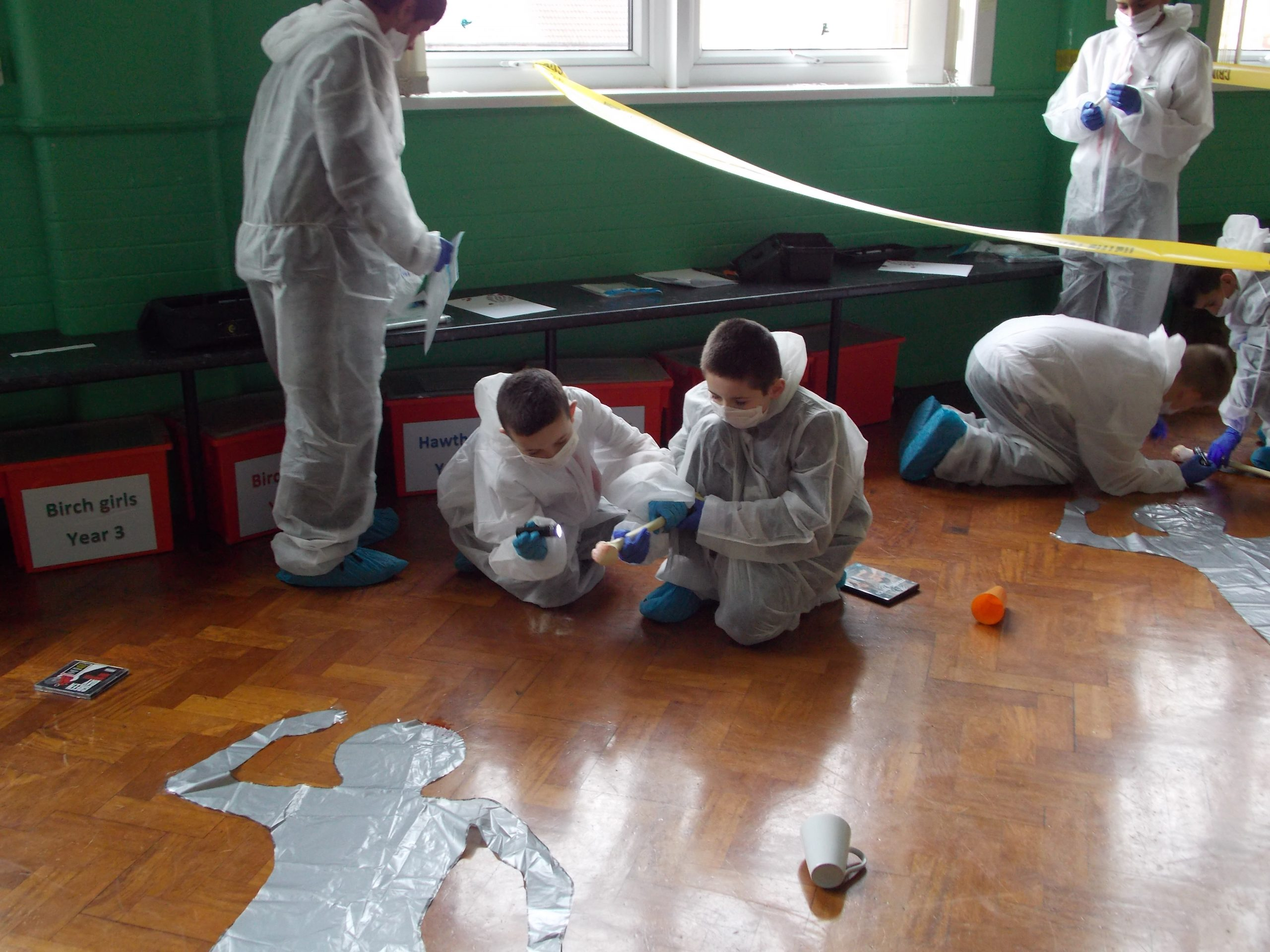 CSI Training and Events - CSI Educational Workshops - Children examining a staged crime scene at a school event