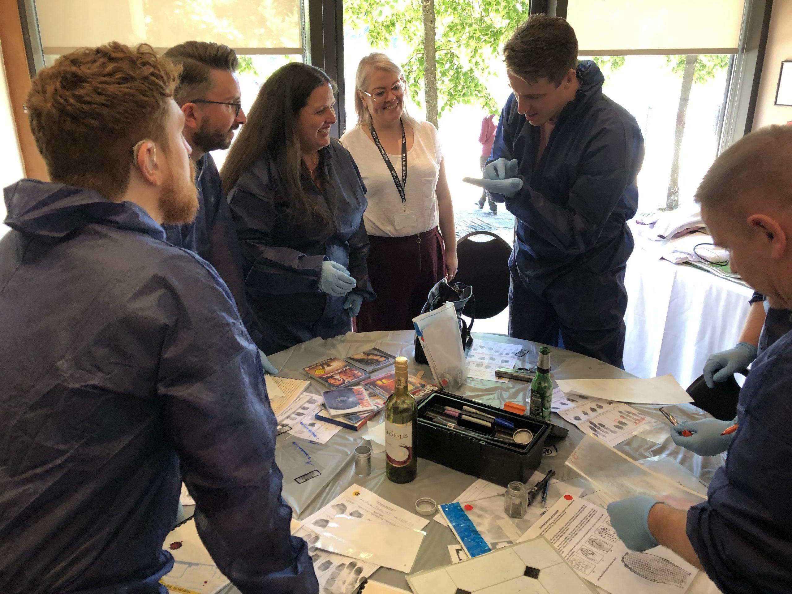 CSI Training and Events - ITV signpost Delegates examining items at a CSI team building event